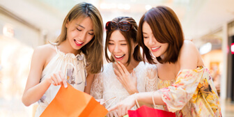 A group of excited women enjoying to shop with the benefits of Citibank year round credit card promotions