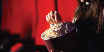 A person enjoying a bucket of popcorn at SF Cinemas where he got a discount with ROP Select card